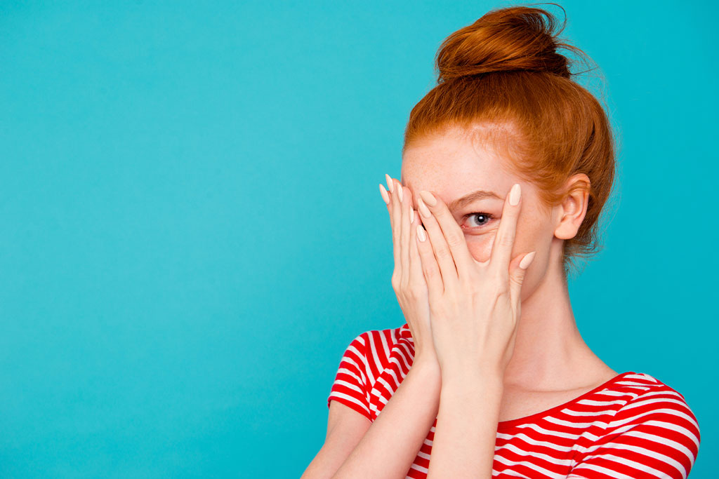 nJoy Vision Blog 10 Common Eye Problems and Treatment Options feature image of a young woman peaking through her fingers