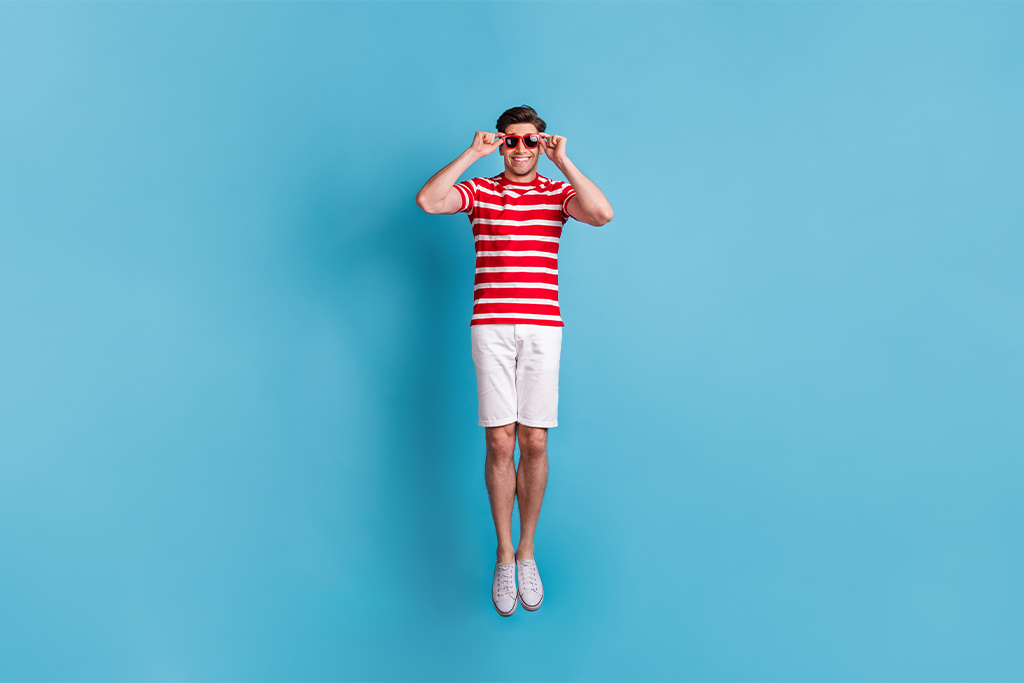 nJoy Vision Eye Health and UV Awareness Month feature image of summery young man jumping with sunglasses