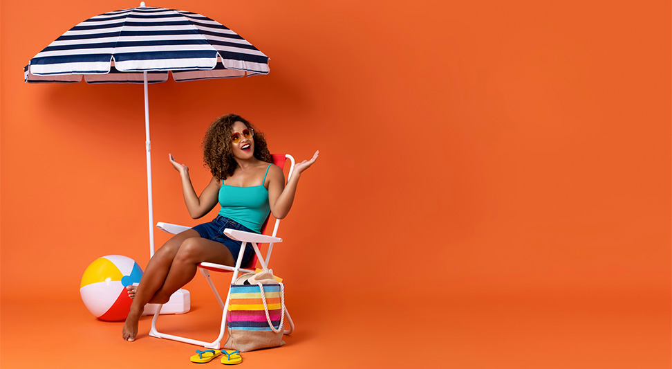 nJoy Vision OKC LASIK Blog UV Safety Awareness Month image of young woman sitting in a lawn chair under a beach umbrella against an orange background